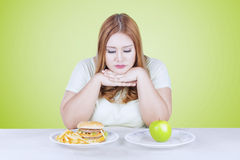 Woman thinks to choose apple or burger Royalty Free Stock Photos