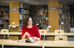 Woman in thought in library looking left Stock Photos
