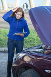 Woman in thought standing near car with tablet pc Stock Image
