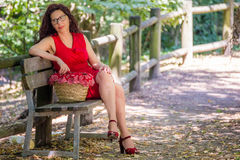 Woman thoughtfully sitting on park bench Stock Image