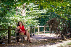 Woman thoughtfully sitting on park bench Stock Photos
