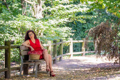 Woman thoughtfully sitting on park bench Stock Images