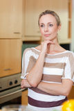 Woman in thoughts standing in kitchen Royalty Free Stock Images