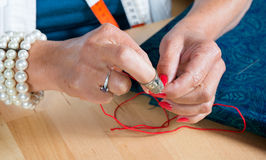 A woman threader the wire in a needle Stock Images