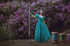 Woman with threads and a needle. Fairy-tale woman holds a large needle in her hand, next to large coils with threads Royalty Free Stock Photography