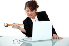 Woman threatening computer with hammer Royalty Free Stock Photography