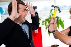 Woman threatening her boss, holding hammer. Stock Photos