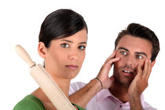 Woman threatening man with rolling pin Stock Photo