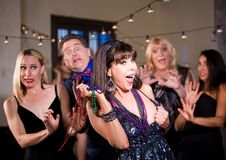 Woman  Threatens to Expose her Breast at a Party. Obnoxious women prepares to flash her breast at a party stock images