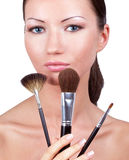 Woman with three professional make-up brushes Royalty Free Stock Photo