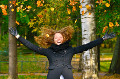 Woman is throwing autumn leaves Stock Photos