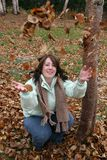Woman throwing Autumn leaves Stock Photos
