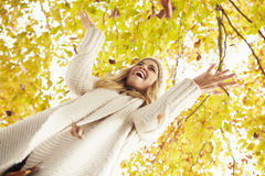 Woman Throwing Autumn Leaves Into The Air Stock Photo