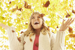 Woman Throwing Autumn Leaves Into The Air Royalty Free Stock Photos