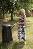 Woman throwing away empty beer bottles Royalty Free Stock Photography