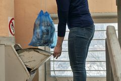 Woman throwing away a garbage packed in a garbage bag using a home garbage chute. In Moscow dwelling house Royalty Free Stock Photography