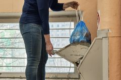 Throwing away a garbage packed in a garbage bag using a home garbage chute. Woman throwing away a garbage packed in a garbage bag using a home garbage chute in Royalty Free Stock Image