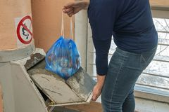 Woman throwing away a garbage packed in a garbage bag using a home garbage chute. In Moscow dwelling house Stock Images