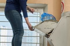 Woman throwing away a garbage packed in a garbage bag using a home garbage chute. In Moscow dwelling house Royalty Free Stock Image