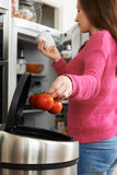 Woman Throwing Away Out Of Date Food In Refrigerator Stock Photos