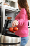 Woman Throwing Away Out Of Date Food In Refrigerator Royalty Free Stock Image