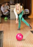 Woman throwing ball in a bowling club Stock Images