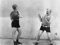 Woman throwing ball to nervous man stock photos