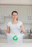Woman throwing bottle into recycling bin Stock Images