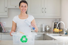 Woman throwing bottle into recycling bin Royalty Free Stock Photography