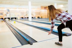 Woman throwing bowling ball. In club Stock Image