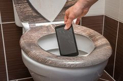 Woman throwing mobile phone in the toilet bowl. Woman throwing broken mobile phone in the toilet bowl royalty free stock photography