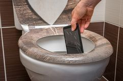 Woman throwing mobile phone in the toilet bowl. Woman throwing broken mobile phone in the toilet bowl stock photos