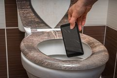 Woman throwing mobile phone in the toilet bowl. Woman throwing broken mobile phone in the toilet bowl stock image