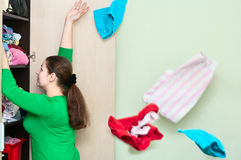Woman throwing a clothes from the wardrobe. Young caucasian woman throwing a clothes from the wardrobe back Royalty Free Stock Photography