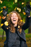 Woman is throwing dry autumn leaves in park Royalty Free Stock Photo
