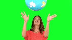 Woman throwing a globe in the air on green screen stock video