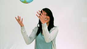 Woman throwing globe in the air stock video