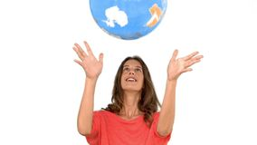 Woman throwing a globe in the air on white background stock footage