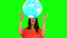 Woman throwing a globe on green screen stock video footage