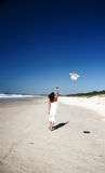 Woman throwing hat in air. Woman throwing hat into air on beach Stock Photography