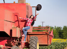 Woman throwing hat from combine harvester Stock Photography