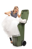 Woman throwing her wedding dress in trash Royalty Free Stock Image