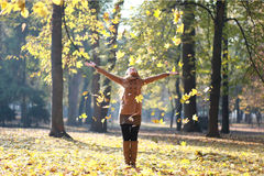 Woman throwing leafs. Young woman playing with leafs in park Royalty Free Stock Photography