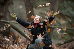 Woman throwing Leaves on the air, enjoying Life,  Outdoor shots Stock Image