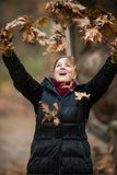 Woman throwing Leaves on the air, enjoying Life,  Outdoor shots Royalty Free Stock Image