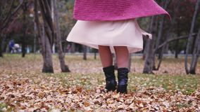 Woman in a beige dress throwing leaves in an autumn fall park having fun in slow motion. View of her legs. 3840x2160, 4k stock video