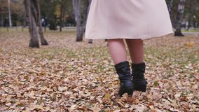 Excited woman throwing leaves spin around in an autumn fall park having fun in slow motion. Close up view of her legs stock video