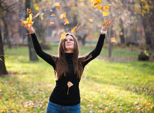 Woman throwing leaves woman in the forest Royalty Free Stock Image
