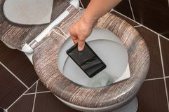 Woman throwing mobile phone in the toilet bowl. Woman throwing broken mobile phone in the toilet bowl royalty free stock photos