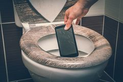 Woman throwing mobile phone in the toilet bowl. Woman throwing broken mobile phone in the toilet bowl - retro style stock photo